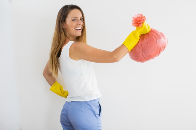 positive-housewife-in-rubber-gloves-with-trash-bag_1262-5397
